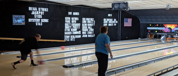 two people standing on the bowling alley, one throwing his ball and the other looking at her lane