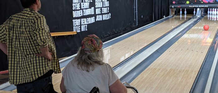 Two Compeer friends together, watching an orange bowling ball go down the lane