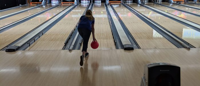 Our program manager Julie in the middle of throwing her bowling ball down the lane